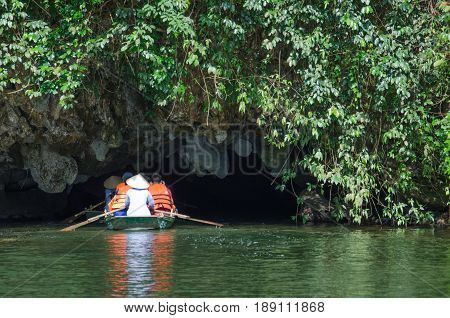 Boat with tourist travel into the cave trang an Vietnam world heritage with moutain and river.