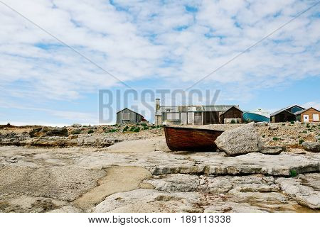 Wooden fishing boat and beach huts next to Portland Bill Lighthouse on the island of Portland, Dorset, against blue sky and clouds on a clear sunny day.