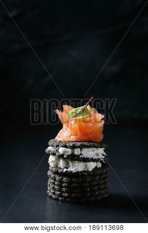 Stack of black wholegrain charcoal crackers with smoked salmon, cream cheese, green salad over black metal background. Appetizer snack. Space for text