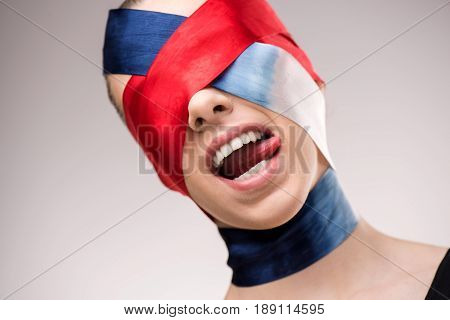 Woman With Wrapped Face With Ribbons Sticking Tongue Out Isolated On Grey