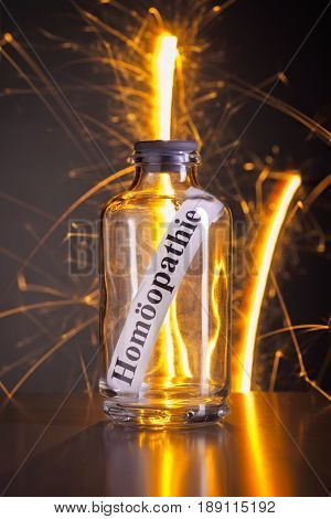 Glass with the word homeopathy and stray sparks