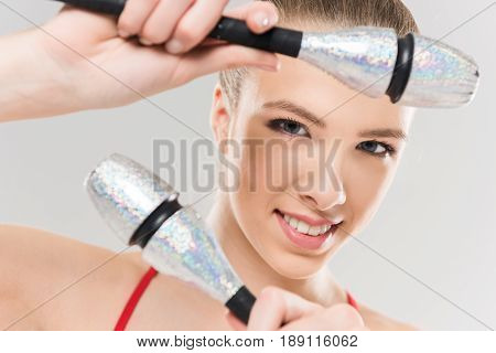 Portrait Of Young Caucasian Woman Rhythmic Gymnast Exercising With Clubs