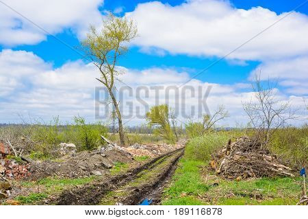 Natural landscape of muddy wheel track of a road with piles of trash