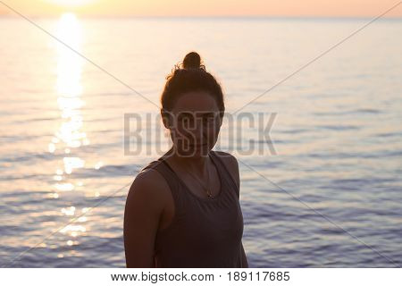 fitness mixed race asian woman in yoga pose on the morning beach, beautiful fit woman practice fitness exrxise stones, morning sea or ocean background