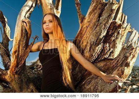 Beautiful woman standing near a dead tree