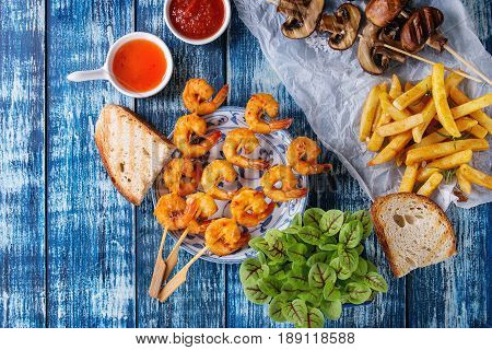 Variety of BBQ snack lunch. Plates grilled spicy king prawn kebabs, mushrooms skewers, bread, french fries potatoes with sauces and greens over blue wooden background. Flat lay