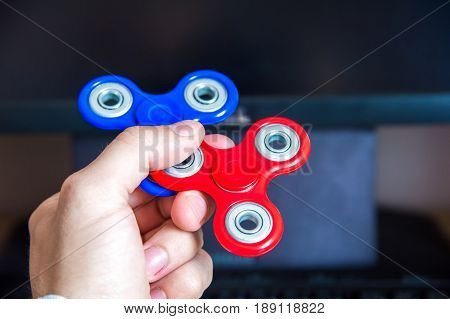 Man's hand holds two multi-colored spinners on the background of a personal computer in office close-up popular fidget spinner toy