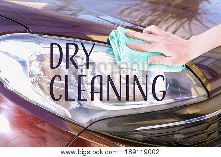 Woman with rag cleaning car headlight. Concept of dry clean