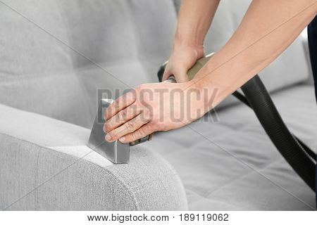 Cleaning service concept. Dry cleaner's employee removing dirt from furniture in flat, closeup