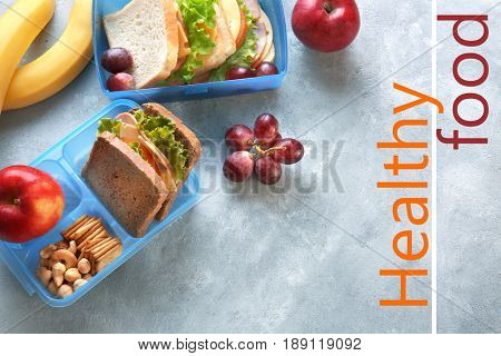 Text HEALTHY FOOD, different products and lunchboxes on gray background