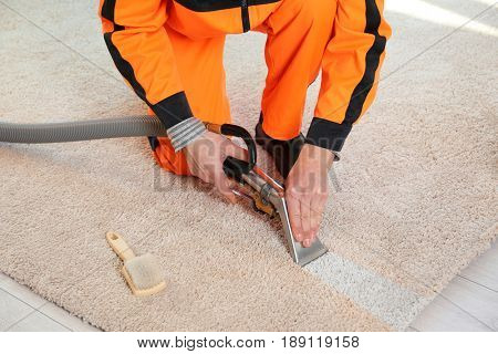 Cleaning service concept. Dry cleaner's employee removing dirt from carpet in flat, closeup