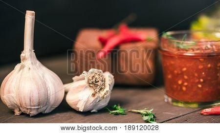 Garlic, red hot chili peppers and potherbs with natural fresh salsa in glass jar on black table