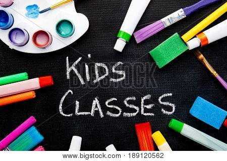 Art - Kids Classes - handwritten on chalkboard surrounded by art equipment