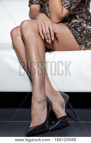 Sexy woman legs in stiletto high heels sitting on sofa