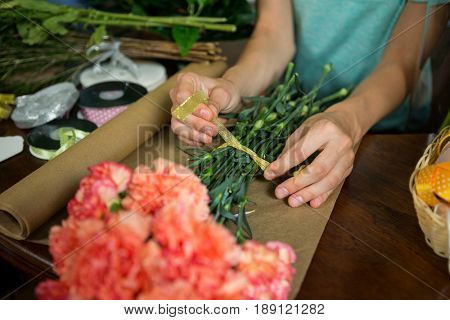Mid-section of female florist preparing bunch of flower in flower shop