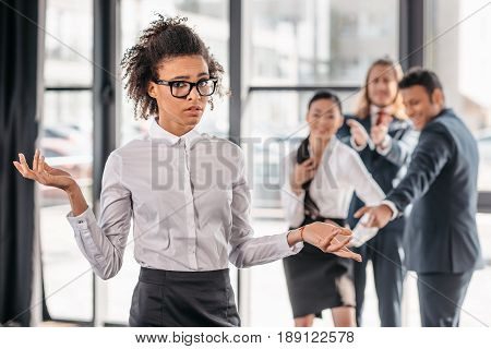 african american businesswoman with shrug gesture businesspeople standing behind and laughing