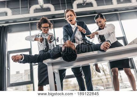 Three Young Angry Businesswomen With Rifle Punishing Businessman Lying On Table, Business Team Meeti