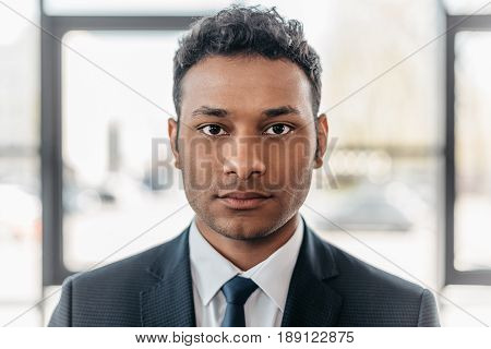 Close-up portrait of young african american businessman in suit looking at camera