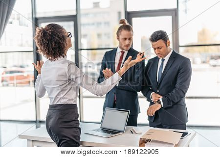 Young Businesswoman Gesturing And Arguing With Coworkers In Office, Business Team Meeting Concept