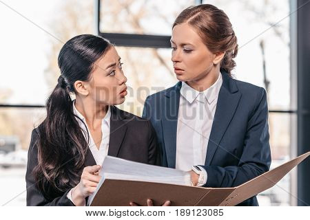 Two young businesswomen working together with folder and looking at each other business team working concept