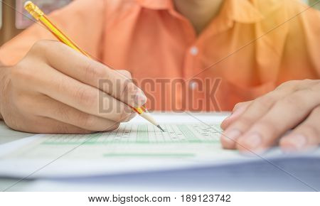 asian students writing test exam on paper for Admissions in high school with uniform student classroom of Thailand exams student background and education concept