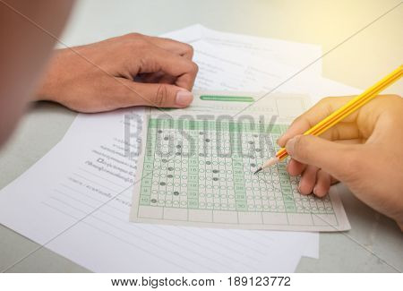 blurred of Asian Thai student testing in exercise exams answer sheets in school