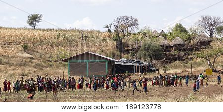 VILLAGE NEAR KONSO OMO VALLEY ETHIOPIA - JANUARY 3 2014: Children and teachers of rural school at a school playground do some sport activities on a break between classes.