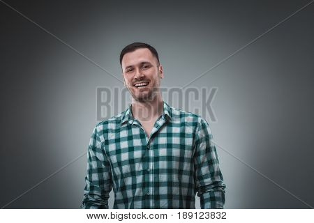 Cheerful man laughing and looking at camera with a big grin. Portrait of a happy young man standing over grey background.