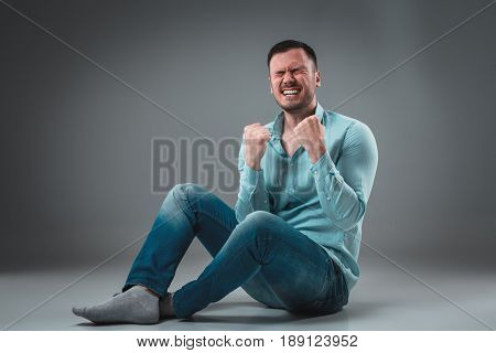 Appealing casual young man sitting on the floor, looking to the camera smiling. Studio shot.