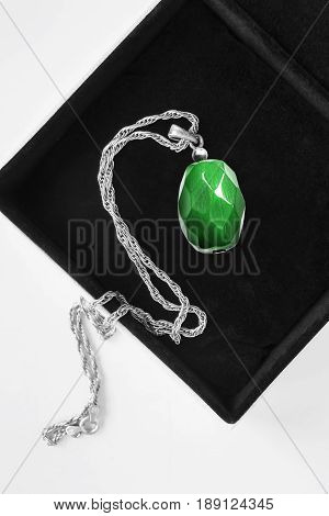 Green malachite faceted pendant on a chain in jewel box closeup