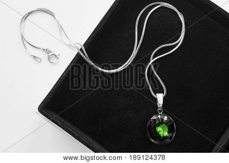 Green crystal pendant on a chain in black jewel box