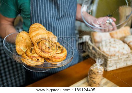 Staff holding tray of croissant at counter in bakery shop