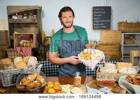Portrait of staff holding bakery snacks at counter in bakery shop