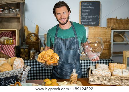 Portrait of staff holding tray of croissant at counter in bakery shop