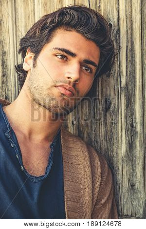 Handsome man relaxing leaning to a wooden wall. The young and attractive man is thoughtful and thinking. Modern hairstyle. Charming casual look. Soft beard.