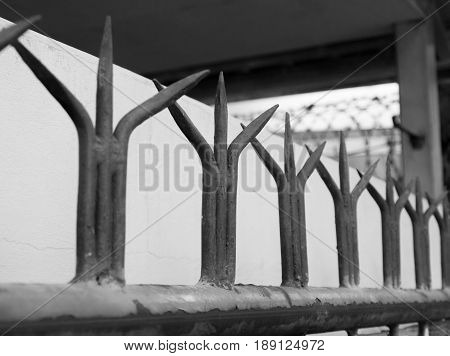 BLACK AND WHITE PHOTO OF RUSTIC RED WROUGHT IRON FENCE