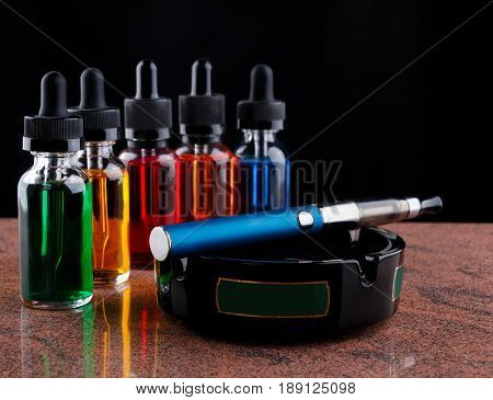 Electronic cigarette on the ashtray and bottles with vape liquid on granite surface. Black background.
