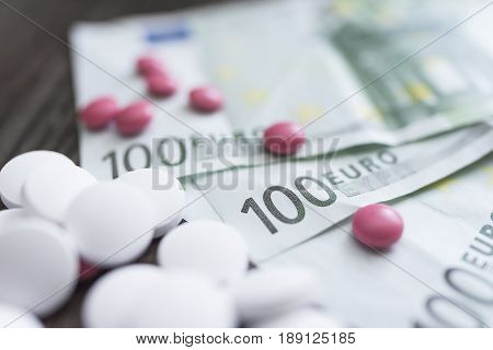 Large white round tablets and small bright pink tablets lie on banknotes of one hundred euros on a dark wooden background.