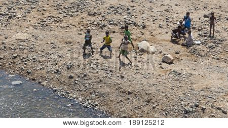 Children Dance On A Dry Riverbed