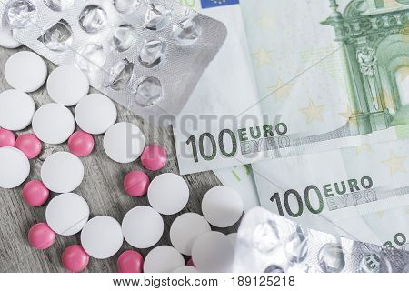 Round white and pink tablets lie next to empty silvery blisters from tablets and monetary denominations of one hundred euros on a wooden background.