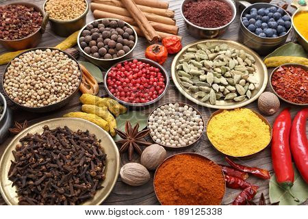 Colorful and aromatic herbs and spices on a wooden background.