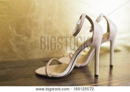 Beige sandals with thin straps on high heels stand on a dark wooden floor against the background of a golden wall.