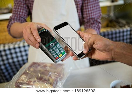 Mid section of man paying through nfc technology at counter in meat shop