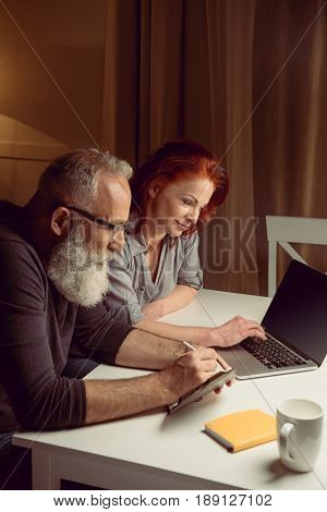 Middle Aged Couple Working On Laptop While Sitting At Table