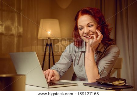 Smiling Mature Red Hair Woman Working On Laptop While Sitting At Table