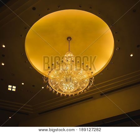 Giant chandelier on glowing yellow circle ceiling like the moon