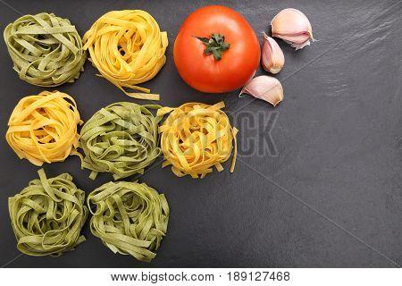 Raw tagliatelle pasta on the black ceramic background.