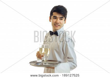 fine young waiter looks away and keeps champagne glasses on a tray that is isolated on a white background