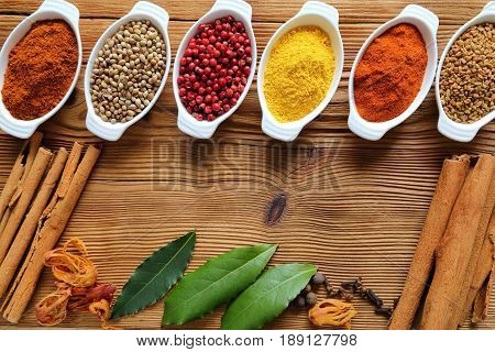 Spices in ceramic containers and wooden bowls. Food and cuisine ingradients.