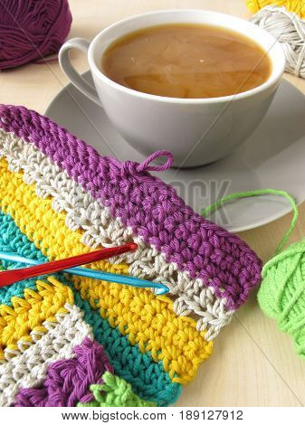 Crochet work and a cup of coffee with milk